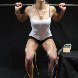 Athlete squatting with four-channel electrical muscle stimulation machine
