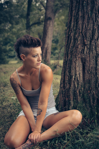Brooke sitting next to a tree in a forest