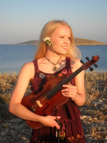 Celka holding a violin at a beach