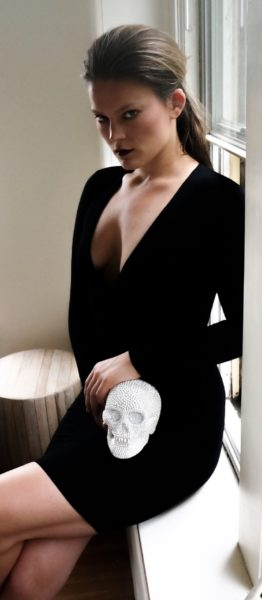 Lydia Mae in a black dress holding a skull